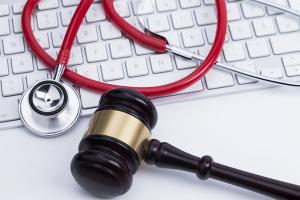 Photograph of stethoscope, gavel, on a computer keyboard