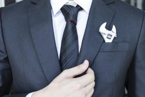 Photograph of man in a suit and tie with wrench in hankerchief pocket