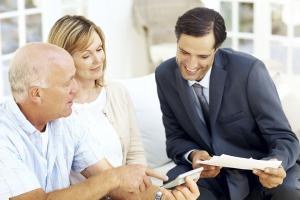 A photograph of a couple with a financial planner